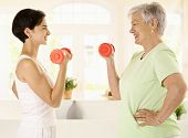 Healthy elderly woman doing dumbbell exercise with personal trainer at home, smiling.?