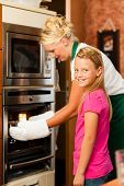 Mother and daughter cooking �¢�?�? they are putting roast in the oven