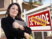 Orgulhoso, atraente agente feminino latino-americano na frente do espanhol Vendido Se Vende Real Estate sinal e Ho