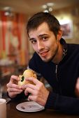 Young man eating burger in fast food restaurant. Shallow DOF.