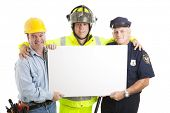 Construction worker, fireman, and policeman holding a blank white sign.  Isolated on white.