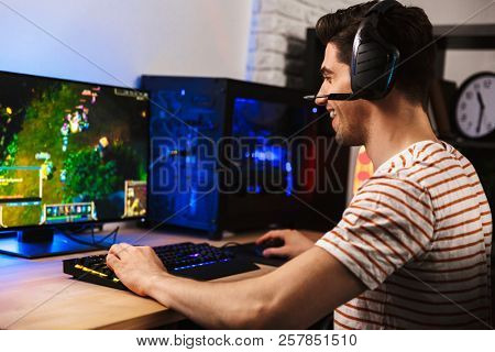 poster of Portrait of professional gamer guy playing video games on computer wearing headphones and using back