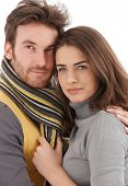 Closeup photo of attractive young loving couple, smiling, looking away.?