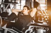 Fit Handsome Caucasian Man Sit Up On Machine In Sportswear. Young Man Sit Up Exercise To Strengthen  poster