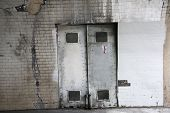 creepy old metal doors. doors to a tunnel entrance poster