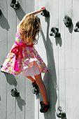 Young Tomboy Girl  in Frilly Dress Climbing Rock Wall