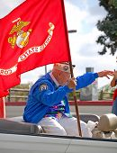 U.S. Military Veteran Holding Marine Corps Flag in Public Parade