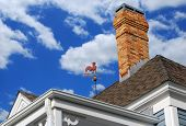 Historic Old Roof with Latticework, Weathervane and Brick Chimney