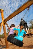 foto of tire swing  - Children Having Fun on Tire Swing - JPG