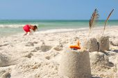 Young girl collecting seashells on beach next to sand castles