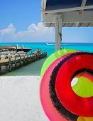 Innertube floats on beach next to doc on pretty ocean
