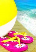 Sandália flipflop colorido e bola de praia inflável pelo Oceano