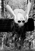 Young tomboy girl upside down on tire swing wearing sunglasses