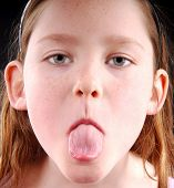 pic of young girls  - Young girl showing displeasure by sticking out tongue - JPG