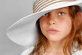 Young freckle faced girl with serious look wearing big hat