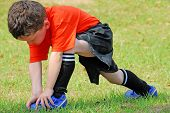 young boy on field stretching before soccer game