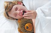 young girl yawning in bed with bear