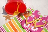 Beach towel, flip flops by bucket and starfish