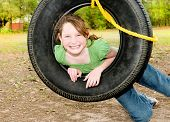 stock photo of tire swing  - Young girl having fun on tire swing - JPG