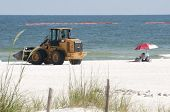 ORANGE BEACH, AL - JUNE 10: A lone beachgoer sits under an umbrella on June 10, 2010 as oil spill workers try to clean up the oil washing ashore at Perdido Pass, AL.