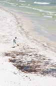 PENSACOLA BEACH - JUNE 23:  A BP oil worker attempts to clean oil covered sand on June 23, 2010 in P