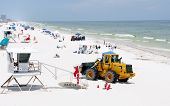 PENSACOLA BEACH - JUNE 23:  BP oil workers and heavy machinery work to clean oil covered sand on Jun