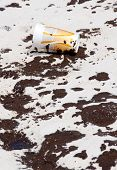 PENSACOLA BEACH - JUNE 23: An oil-stained cup lies near oil covered sand on June 23, 2010 in Pensacola Beach, FL