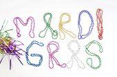 mardi gras written in throwing beads