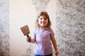 Adorable Little Girl Repairing Wall In Apartment, Holding Putty Knife Old Wall At The Background. Em poster