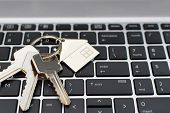 Three Metal Keys With Keychain And House Shape Pendant On Black Laptop Keyboard.  Online House Renta poster