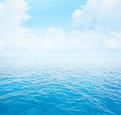 Blue clear sea with waves and sky with fluffy clouds poster