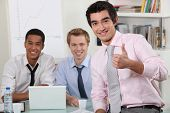 male trio in meeting room with laptop
