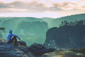 Hiker Is Enjoying Sunrise View In Hilly Landscape. Male Hiker Sitting And Relaxing At The Rocky Summ poster