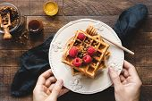 Eating Waffles For Breakfast. Person Holding Plate Of Belgian Waffles With Raspberries, Granola And  poster