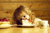 Cute Little Boy Child With Long Blonde Hair Eating Tasty Creamy Pie Or Cake With Red Strawberry Frui poster