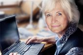 pic of senior adult  - Senior lady ready to start her laptop - JPG