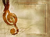 Musical background in vintage style - sheet music with wooden treble clef and notes on old paper tex
