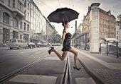 Beautiful woman running under an umbrella on a city street