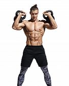 Young Muscular Guy Training With Kettlebells. Photo Of Sporty Model With Naked Torso And Good Physiq poster