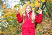 Cheerful Schoolgirl. Child Blonde Long Hair Walking In Warm Jacket Outdoor. Girl Happy In Red Coat E poster