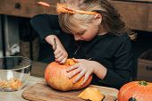 Cute Kid Carving Pumpkin For Halloween Alone At Tabletop At Home poster