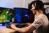 Portrait of professional gamer guy playing video games on computer wearing headphones and using back poster