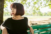Young Asian Woman Sitting Alone On The Public Bench In The Park Surrounded With Nature And Warm Sunl poster