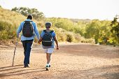 Rear View Of Senior Couple Wearing Backpacks Hiking In Countryside Together poster