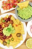 An Overhead Photo Of Mexican Dishes. Nachos With Chili Con Carne And Cheese, Guacamole With A Totopo poster