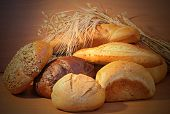 Group of bread and wheat spikes on wooden background.