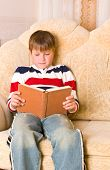 boy reads book on sofa