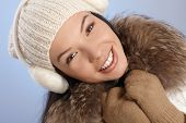Winter portrait of beautiful smiling young woman in white cap and earmuffs.