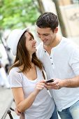 Couple in town using smartphone and handsfree device