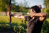 foto of archer  - Young archer training with the  bow - JPG